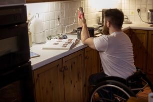 Disabled man repairing a pan in kitchenの写真素材 [FYI02241579]