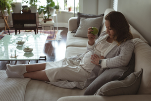 Pregnant woman relaxing on sofa in living roomの写真素材 [FYI02241606]
