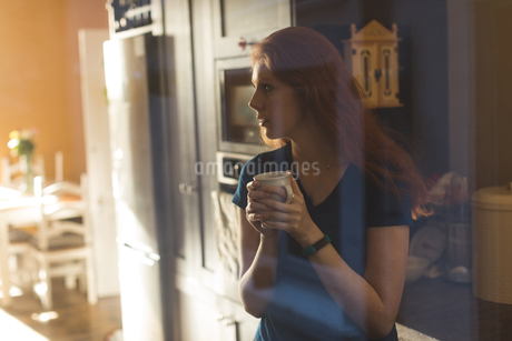 Woman having coffee in kitchen at homeの写真素材 [FYI02241639]
