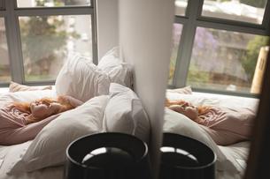 Woman relaxing on bed in bedroomの写真素材 [FYI02241652]