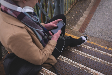Woman sitting on stairs and using mobile phoneの写真素材 [FYI02241659]