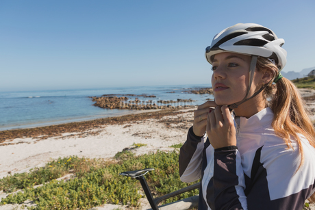 Female biker wearing her helmet near beachの写真素材 [FYI02241660]