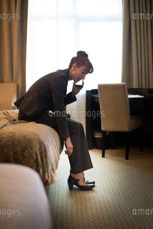 Businesswoman talking on mobile phone while wearing shoesの写真素材 [FYI02241663]