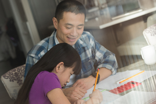 Father assisting her daughter in doing homeworkの写真素材 [FYI02241693]