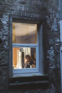 Woman having coffee while using mobile phoneの写真素材 [FYI02241709]