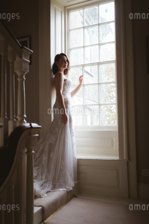 Bride standing at the window at homeの写真素材 [FYI02241711]