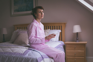 Thoughtful woman holding digital tablet on bedの写真素材 [FYI02241734]
