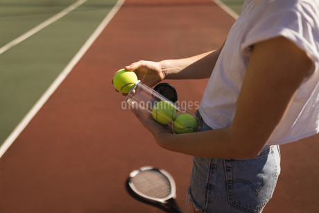Woman removing tennis ball from tennis ball caseの写真素材 [FYI02241773]