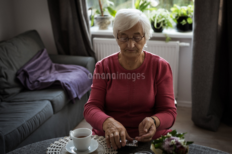 Senior woman looking at medicines in living roomの写真素材 [FYI02241775]