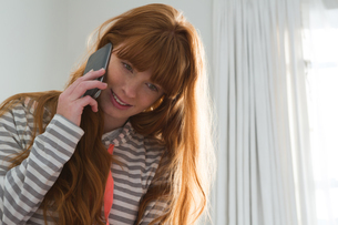 Woman talking on mobile phone in bedroomの写真素材 [FYI02241786]