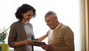 Caretaker showing digital tablet to senior womanの写真素材 [FYI02241829]