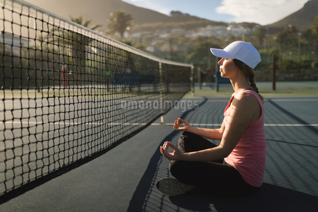 Woman performing yoga exercise in tennis courtの写真素材 [FYI02241839]