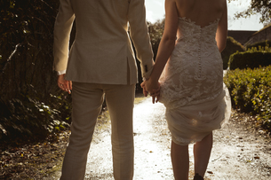 Bride and groom walking hand in hand in the gardenの写真素材 [FYI02241842]