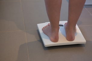 Woman checking her weight on weighing scales at homeの写真素材 [FYI02241845]