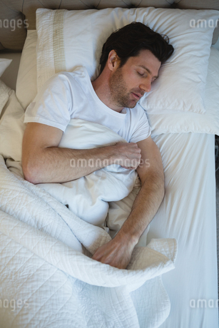 Man sleeping in bedroomの写真素材 [FYI02241869]