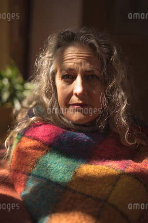 Portrait of mature woman wrapped in blanketの写真素材 [FYI02241885]