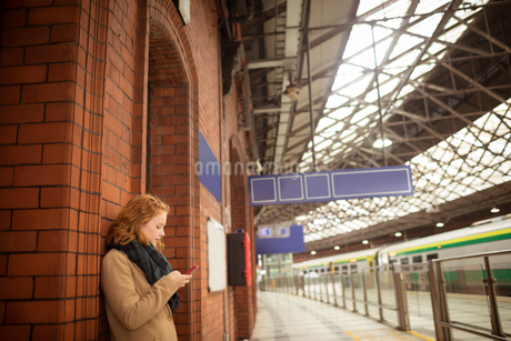 Woman using mobile phone at railway stationの写真素材 [FYI02241896]