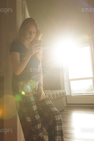 Woman using mobile phone in living roomの写真素材 [FYI02241928]