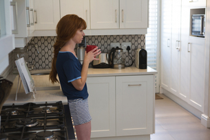 Woman having coffee in kitchen at homeの写真素材 [FYI02241929]