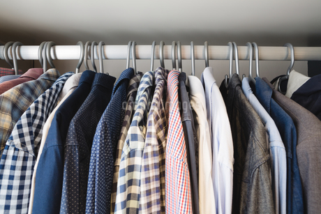 Various shirts hanging in hangers at homeの写真素材 [FYI02241963]