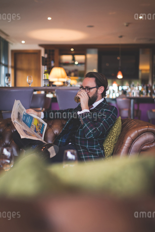 Businessman reading newspaper while having whiskyの写真素材 [FYI02241989]