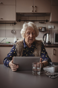Senior woman using digital tablet in the kitchenの写真素材 [FYI02241992]