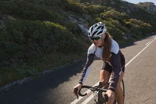 Biker riding mountain bike on roadの写真素材 [FYI02242003]