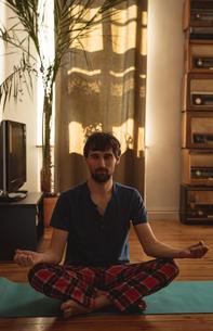 Man practicing yoga in living roomの写真素材 [FYI02242007]