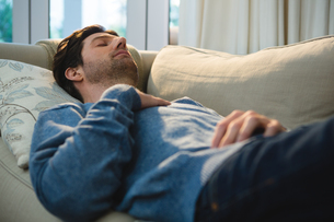 Man sleeping on sofa in living roomの写真素材 [FYI02242016]