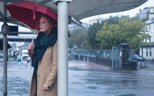 Young woman holding an umbrella standing at bus stopの写真素材 [FYI02242021]