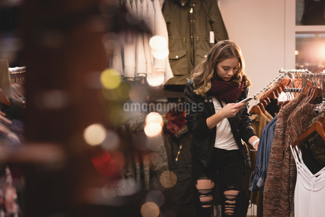 Beautiful woman using mobile phone while shoppingの写真素材 [FYI02242040]