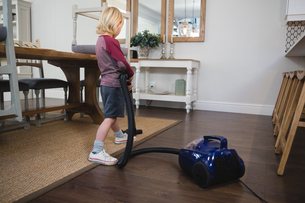 Boy using vacuum cleaner in living roomの写真素材 [FYI02242045]