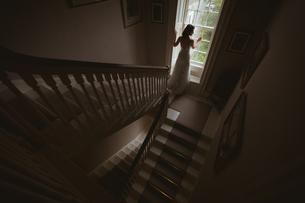 Bride standing at the window at homeの写真素材 [FYI02242052]