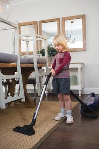Boy using vacuum cleaner in living roomの写真素材 [FYI02242074]