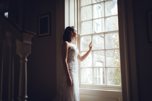 Bride looking out of the window at homeの写真素材 [FYI02242108]