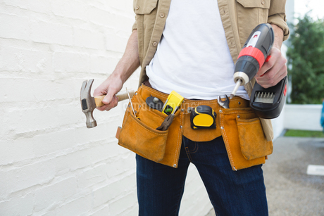 Male carpenter with tool belt holding hammer and drill machineの写真素材 [FYI02242144]