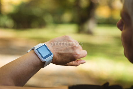 Senior woman using a smart watch in a park on a sunny dayの写真素材 [FYI02242146]