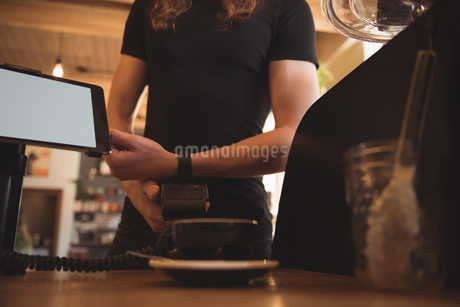 Customer making payment with smartwatch at counterの写真素材 [FYI02242156]
