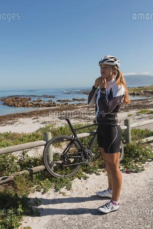 Female biker wearing her helmet near beachの写真素材 [FYI02242163]