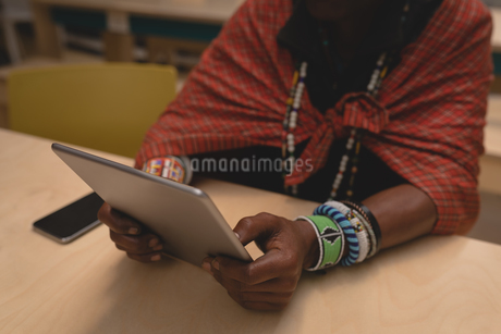 Maasai man in traditional clothing using digital tabletの写真素材 [FYI02242192]