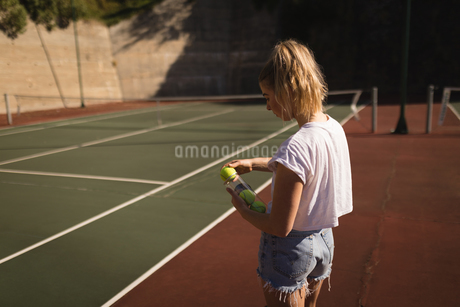 Woman removing tennis ball from tennis ball caseの写真素材 [FYI02242213]