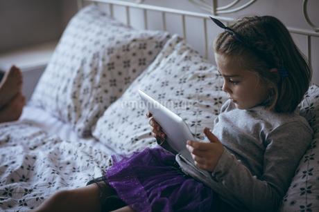 Girl using digital tablet on bedの写真素材 [FYI02242218]