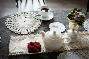 Cup of tea with raspberry bowl and tea pot on tableの写真素材 [FYI02242221]