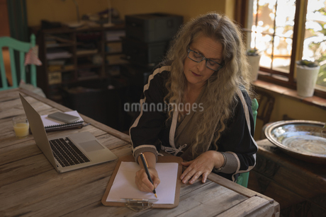 Mature woman sitting on chair and writing on paperの写真素材 [FYI02242241]