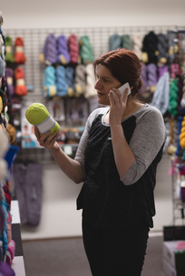 Woman looking at yarn while talking on mobile phoneの写真素材 [FYI02242256]
