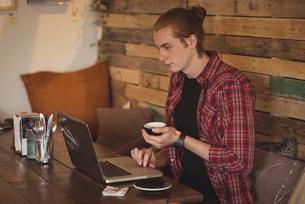 Man using laptop while having coffeeの写真素材 [FYI02242305]
