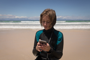 Close-up of teenage girl in wetsuit using mobile phoneの写真素材 [FYI02242311]
