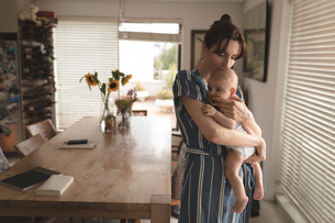 Young mom in bath rob holding and kissing her baby in living roomの写真素材 [FYI02242331]