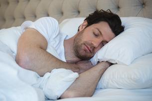 Man sleeping in bedroomの写真素材 [FYI02242354]