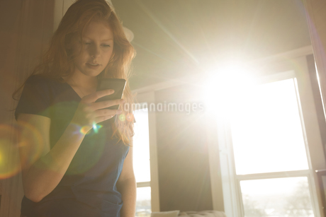 Woman using mobile phone in living roomの写真素材 [FYI02242419]